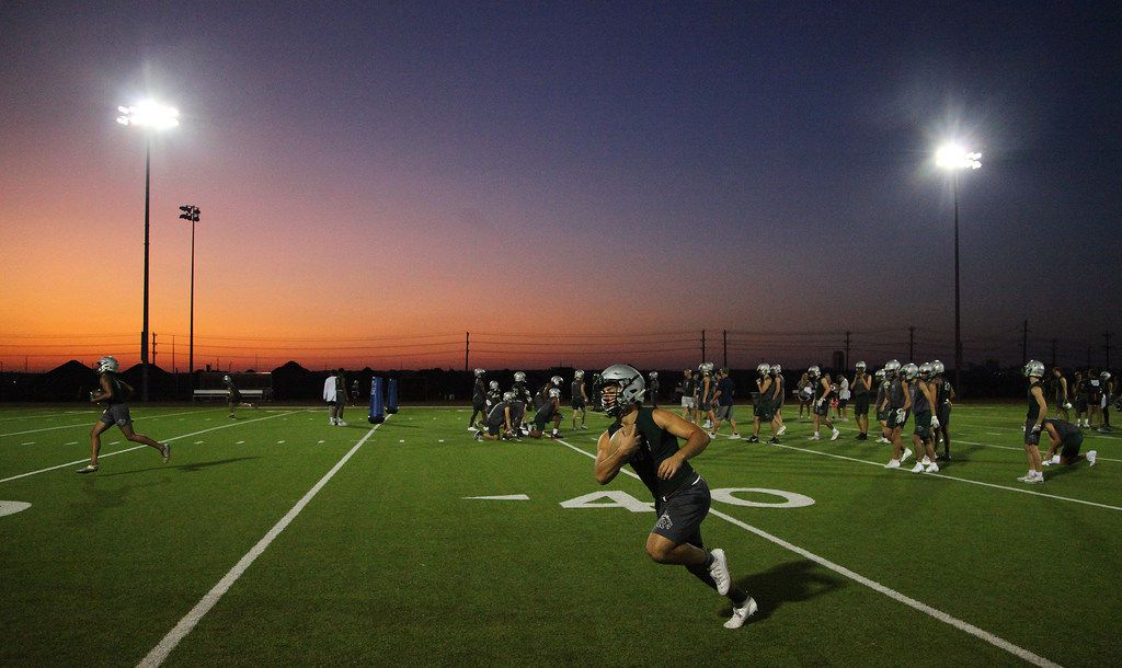 Sam Noskin, 16, runs after the catch as the sun begins to rise during football practice at Reedy High School in Frisco which started at 5:30 a.m on Monday, August 12, 2019 to avoid the hotter daytime temperatures.   Players reported to the locker room at 5:30 am, and the practice began at 6 am. (Stewart House/Special contributor)
