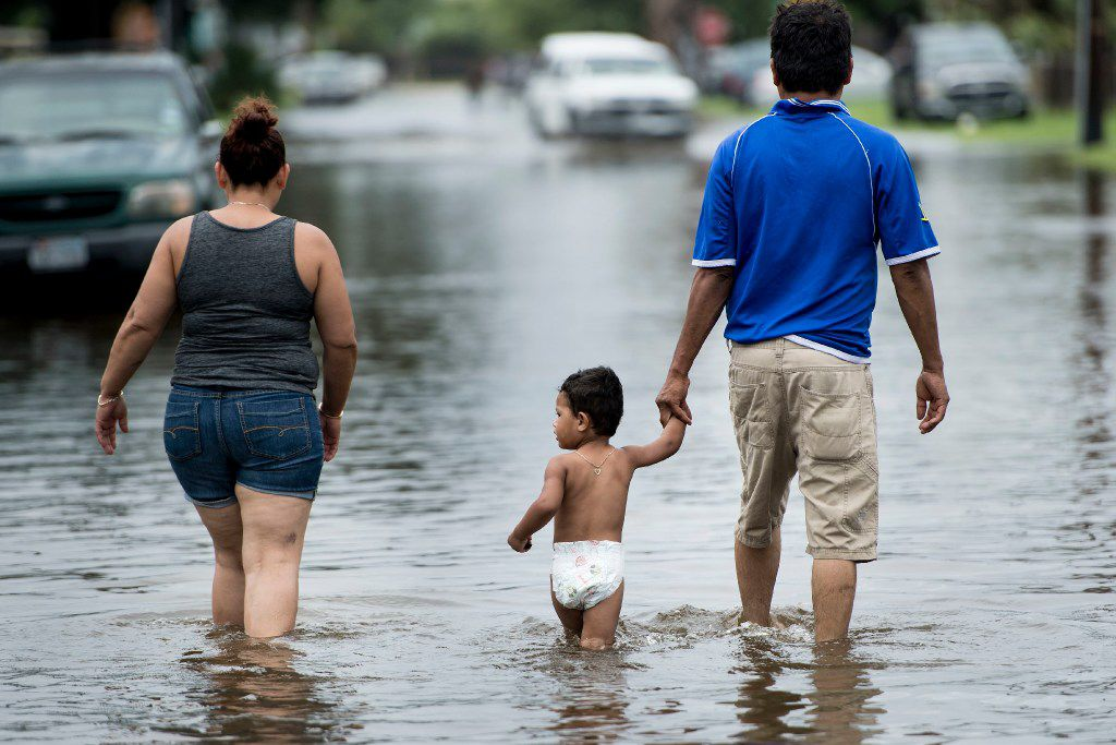 People walk through flooded streets as the effects of Hurricane Henry are seen August 26, 2017 in Galveston, Texas. Hurricane Harvey left a trail of devastation Saturday after the most powerful storm to hit the US mainland in over a decade slammed into Texas, destroying homes, severing power supplies and forcing tens of thousands of residents to flee.