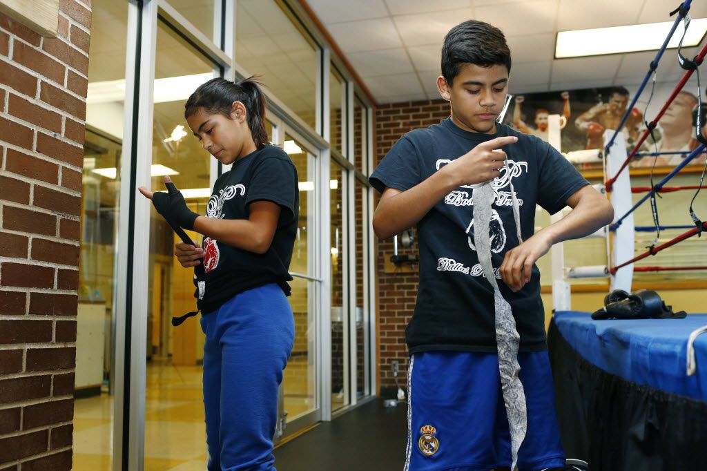 Candice Badillo, 11, (left) and Oliver Badillo, 13, wrap their wrists before practice with the Dallas Police Athletic League boxers at JC Turner Recreation Center in Dallas Thursday, June 18, 2015. (Nathan Hunsinger/The Dallas Morning News)