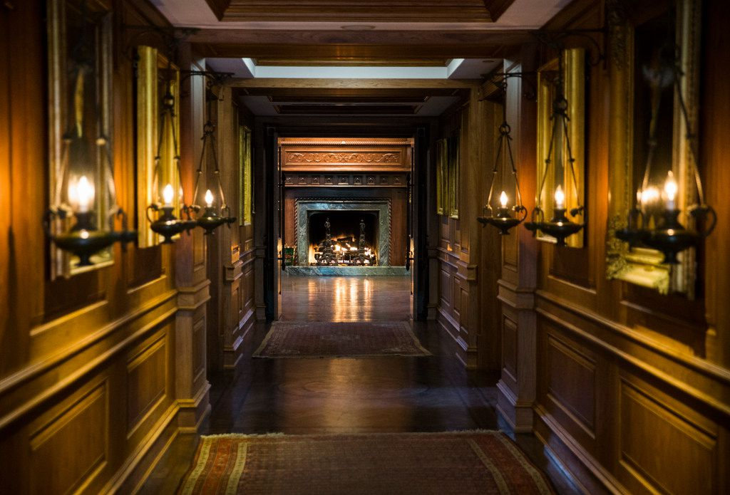 A hallway lit with lanterns and decorated with gold-leaf framed oil portraits leads to a fireplace in the Pecan Room inside the old nurses quarters building at Old Parkland in Dallas. The original hospital and nurses quarters were converted to office space, and several new buildings have been added to the complex.