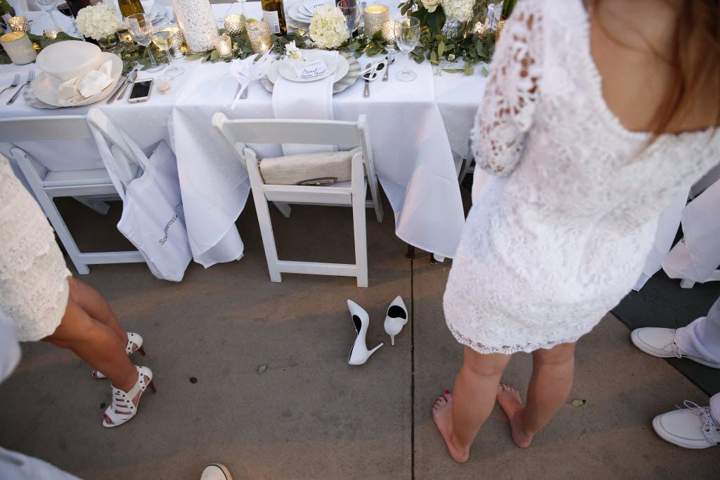 Laura West takes off her shoes during the inaugural Diner en Blanc Dallas on the Continental Avenue Bridge in Dallas on Sept. 17, 2015. Exactly 1,678 people attended the event, which requires dinner guests to dress all in white and bring their own tables, chairs and centerpieces. As per tradition, the location was kept private leading up to the event.