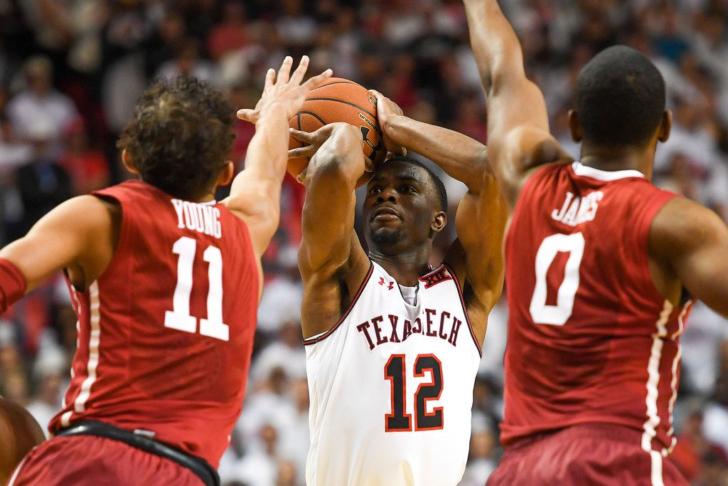 LUBBOCK, TX - FEBRUARY 13: Keenan Evans #12 of the Texas Tech Red Raiders shoots the ball over Trae Young #11 and Christian James #0 of the Oklahoma Sooners during the second half of the game on February 13, 2018 at United Supermarket Arena in Lubbock, Texas. Texas Tech defeated Oklahoma 88-78. (Photo by John Weast/Getty Images)