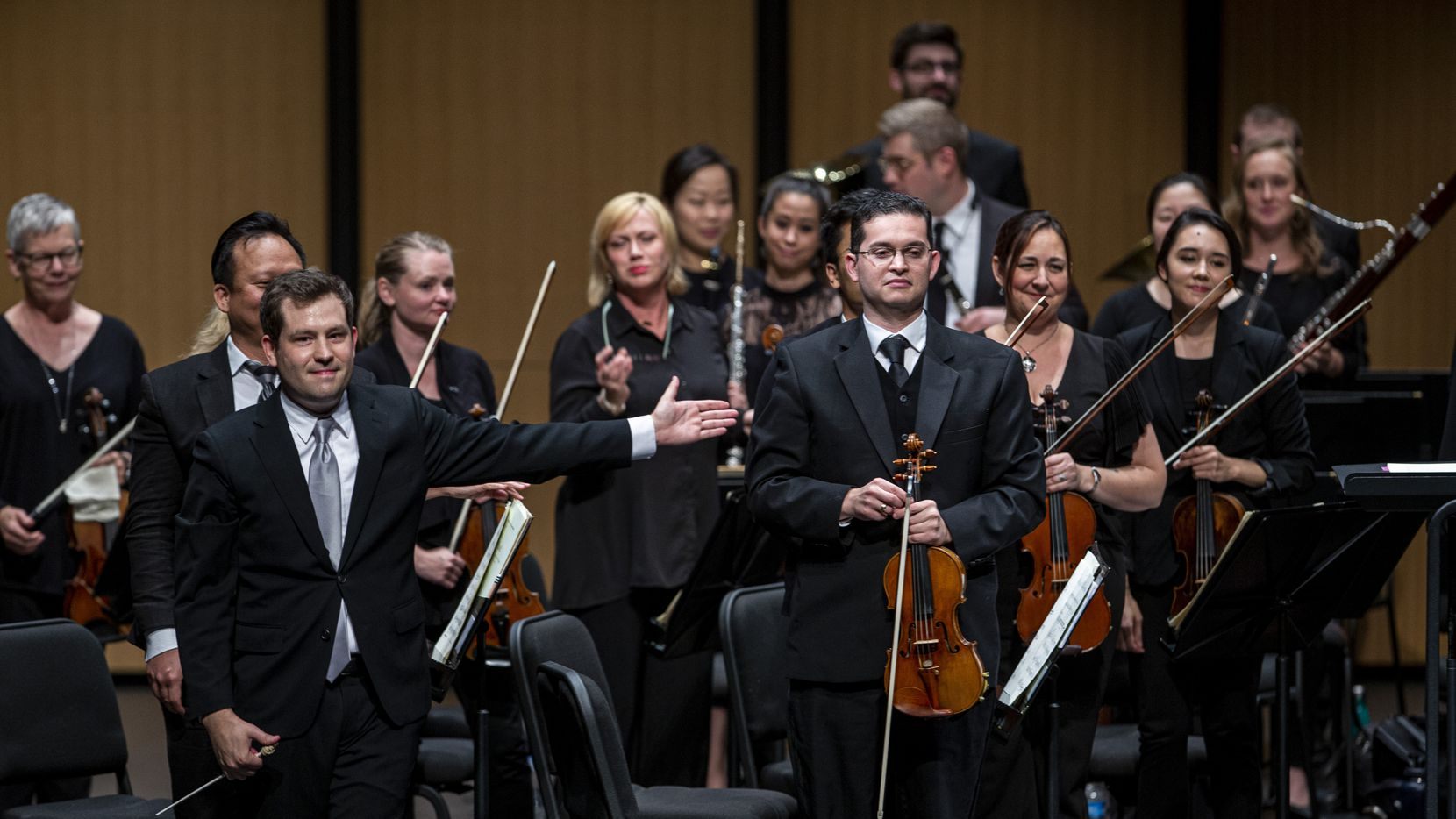 Conductor Richard McKay (left) directs the audiences applause towards violinist Simon Gollo during the season-opening concert by the Dallas Chamber Symphony at Moody Performance Hall in Dallas Oct. 22, 2019.
