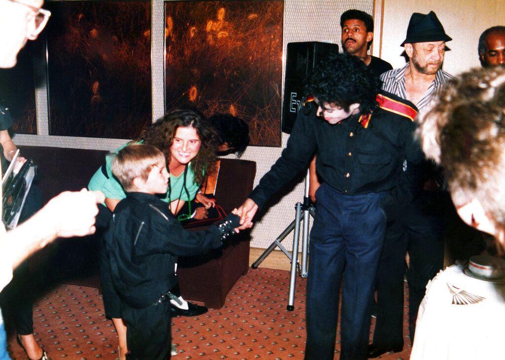 """En esta imagen difundida por HBO, un joven Wade Robson estrecha la mano de Michael Jackson en 1987, en una escena del documental """"Leaving Neverland"""". (Dan Reed/HBO vía AP)"""