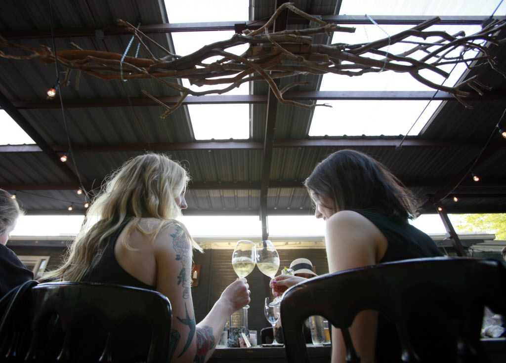 Liz Scobee, left, and Havana Hernandez, cheers their champagne glasses before dinner at a pop-up location for Uchi restaurant during a preview dinner.