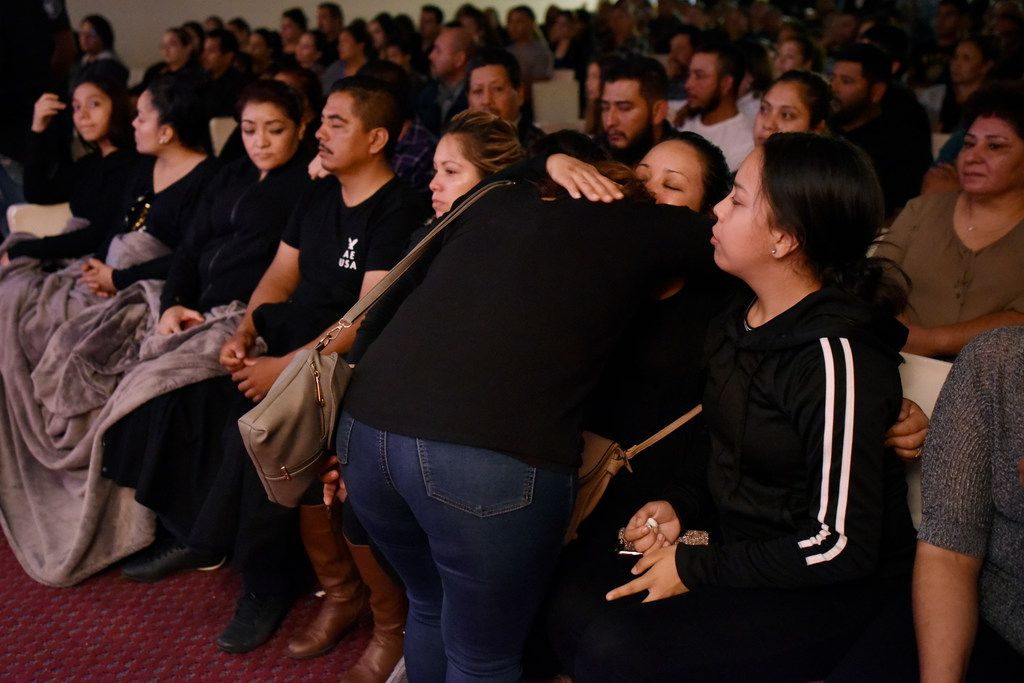 A mourner hugs Raul Ortega Cabrera's widow during the viewing.