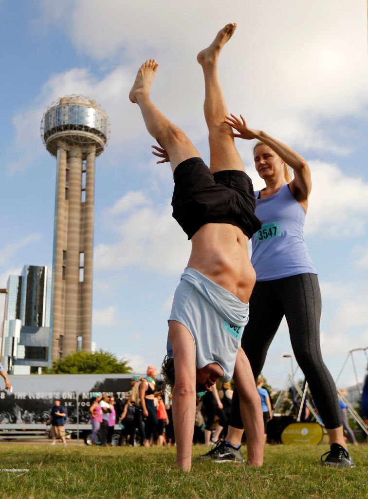 Christina Clark of Houston helps her friend Daan Veeningen do a handstand before Reunion Tower as they participate in the Wanderlust yoga and mediation session in Dallas.