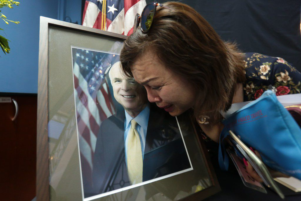 Mai Tran, an American of Vietnamese descent, grieves over the portrait of Sen. John McCain during a memorial tribute at the U.S. embassy in Hanoi on Aug. 27, 2018.