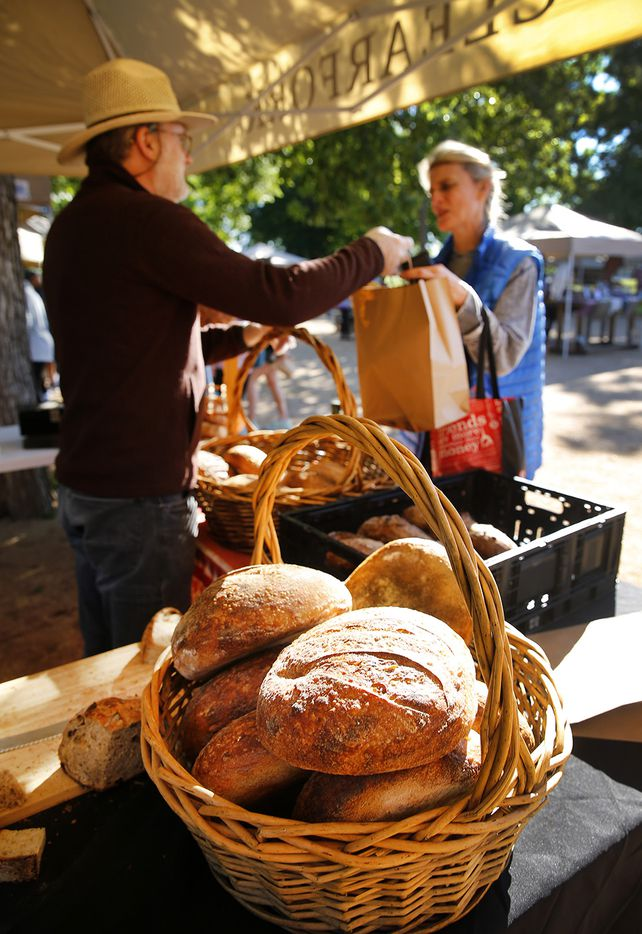 Icon Bread owner Trent Shaskan sells some of his sourdough bread to Alison Robinson of Fort Worth at the Farmers Market which is open on Saturday mornings at The Trailhead at Clearfork in Fort Worth.