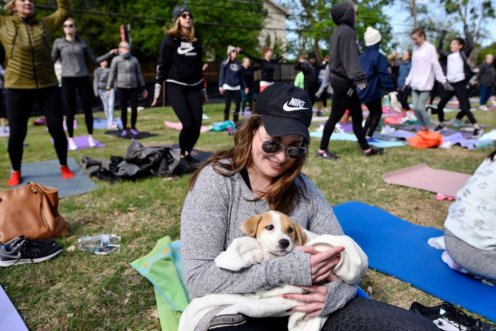 Logan Kearins, 29, of Dallas, comforts a puppy from Operation Kindness as the pup took a break from Puppy yoga, near the Northaven Trail in Dallas, Saturday morning, April 14, 2018. The yoga was conducted by CorePower Yoga and a portion of the proceeds benefited the Dallas based non-profit Artists for Animals. Puppies were provided by Operation Kindness.