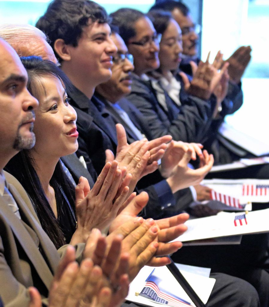 New U.S. citizens applaud during a naturalization ceremony at the Amon Carter Museum of American Art in Fort Worth.
