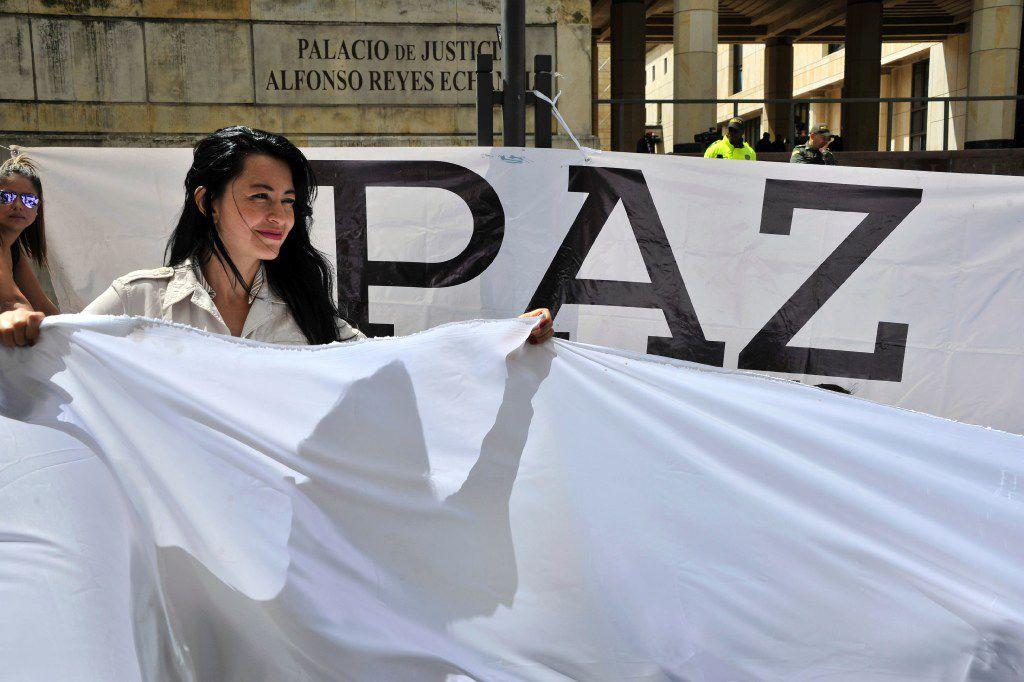 Una mujer sostiene una bandera blanca durante una manifestación para exigir el respaldo inmediato del acuerdo de paz entre el gobierno colombiano y la guerrilla de las FARC. (AP)