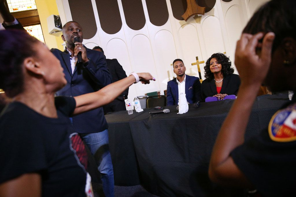 Melissa Perry (far left) shouts at Dallas County District Attorney Faith Johnson, who is seated next to Dallas attorney Justin Moore, regarding a question about Amber Guyger's charge, during a town hall panel regarding action taken following the death of Botham Jean, who was shot and killed by fired Dallas police officer Amber Guyger, at St. Paul United Methodist Church in Dallas on Saturday, Sept. 29, 2018. (Rose Baca/The Dallas Morning News)