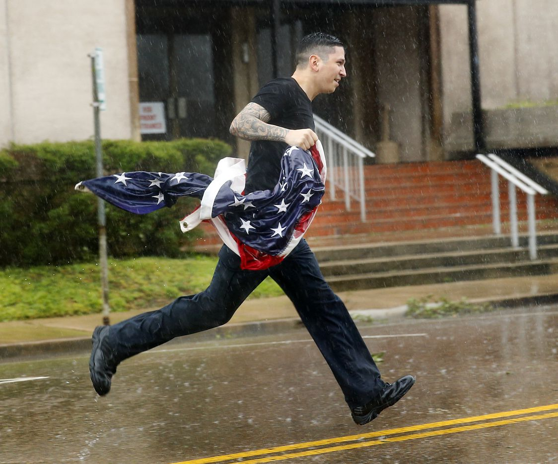 Victoria, Texas senior police officer Cody Balli secured the American flag after it blew down in front of the Victoria County Courthouse.