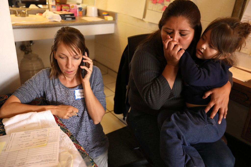 Annunciation House volunteer Rachel Soltis (left) gets in touch with Leslie Angelia's family in Los Angeles to arrange a bus ticket for her and her daughter Argelee Yulieth, 3, a day after the pair were released from detention at a motel in El Paso, Texas, on October 23, 2018.