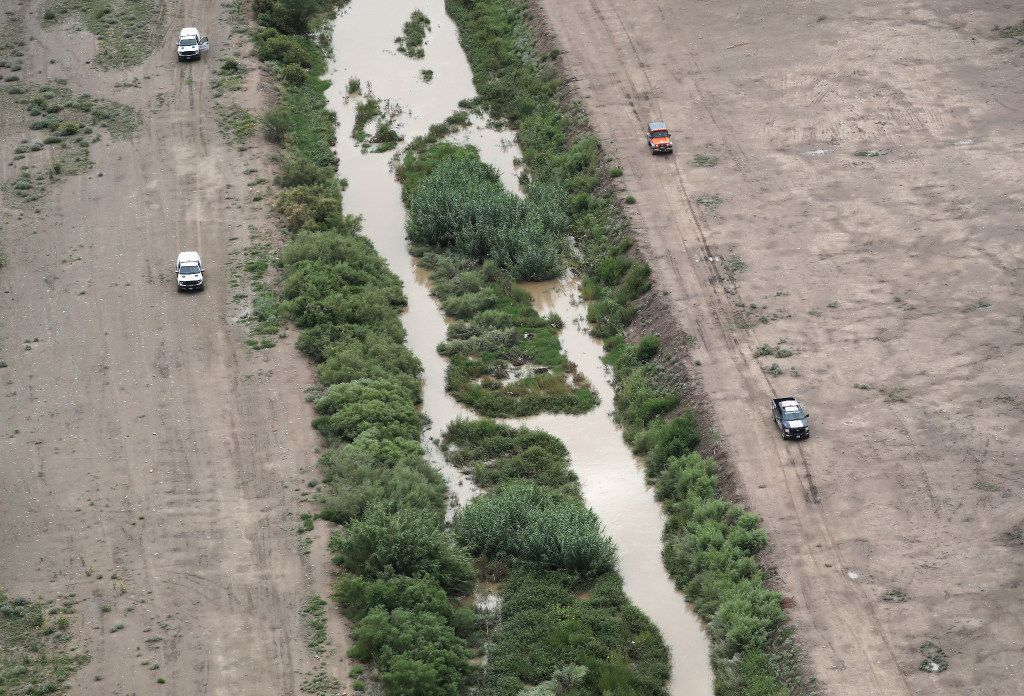 EL PASO, TX - AUGUST 01: U.S. Border Patrol (L), and Mexican immigration agents perform a joint patrol along the Rio Grande at the U.S.-Mexico border as seen from a U.S. Customs and Border Protection helicopter on August 1, 2017 in El Paso, Texas. Logistical challenges are just some of the complications facing the construction of a border wall proposed by President Trump.