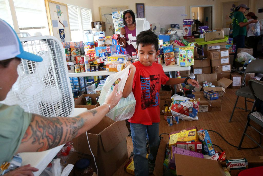Volunteer Aiden Levario, 7, sorts through donated goods at the Trinity by the Sea Episcopal Church in Port Aransas on Saturday, Sept. 2, 2017. The coastal region suffered severe damage after Hurricane Harvey hit the area on Aug. 26, 2017. (Rose Baca/The Dallas Morning News)