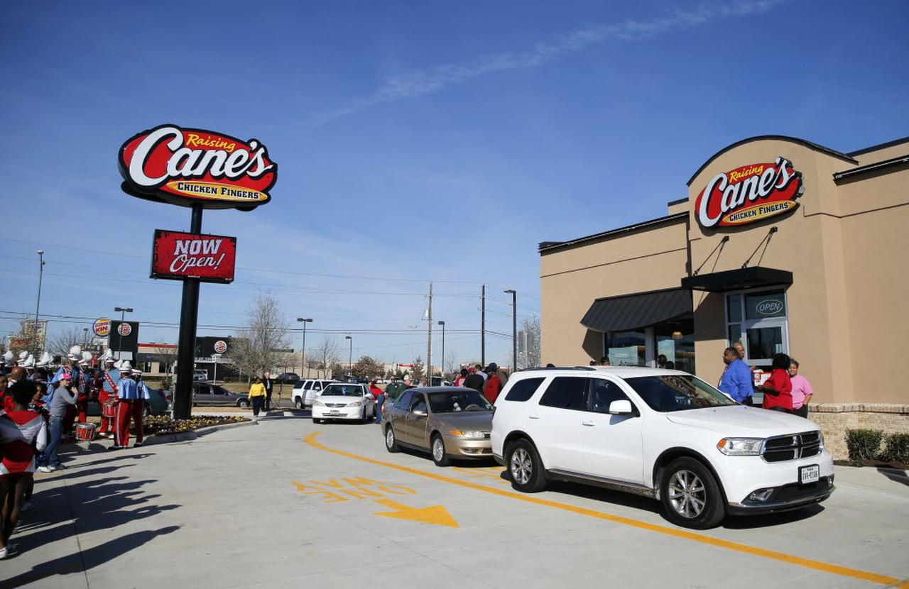 Cars line up as the Carter High School band plays during the grand opening of a Raising Cane's in Dallas on Tuesday, February 16, 2016. Members of the community have spoken out against businesses such as pay-day lenders in the area, pushing for more community friendly businesses.