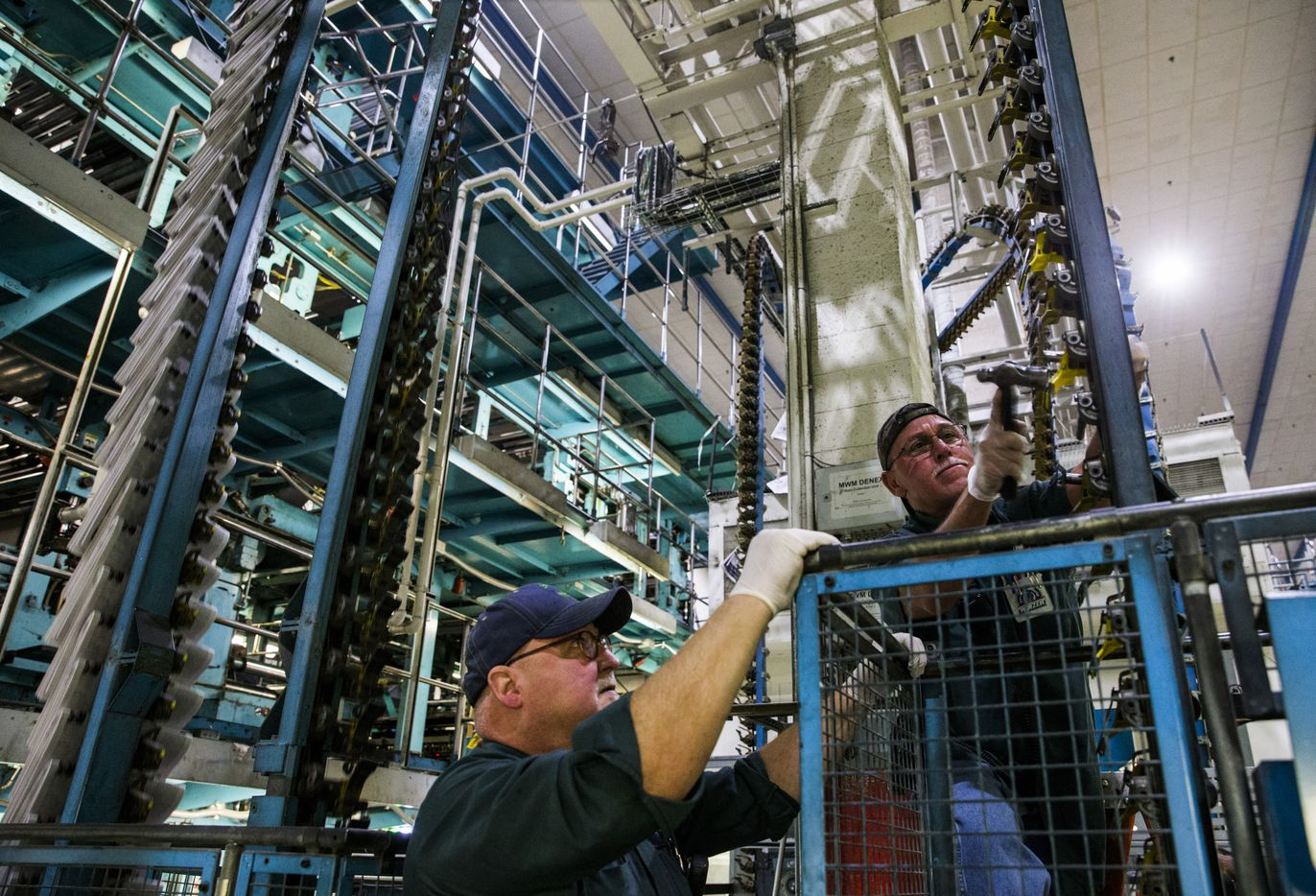 Joe Stockroom, left, and Hector Quinones do maintenance on a printing press. (Ashley Landis/The Dallas Morning News)