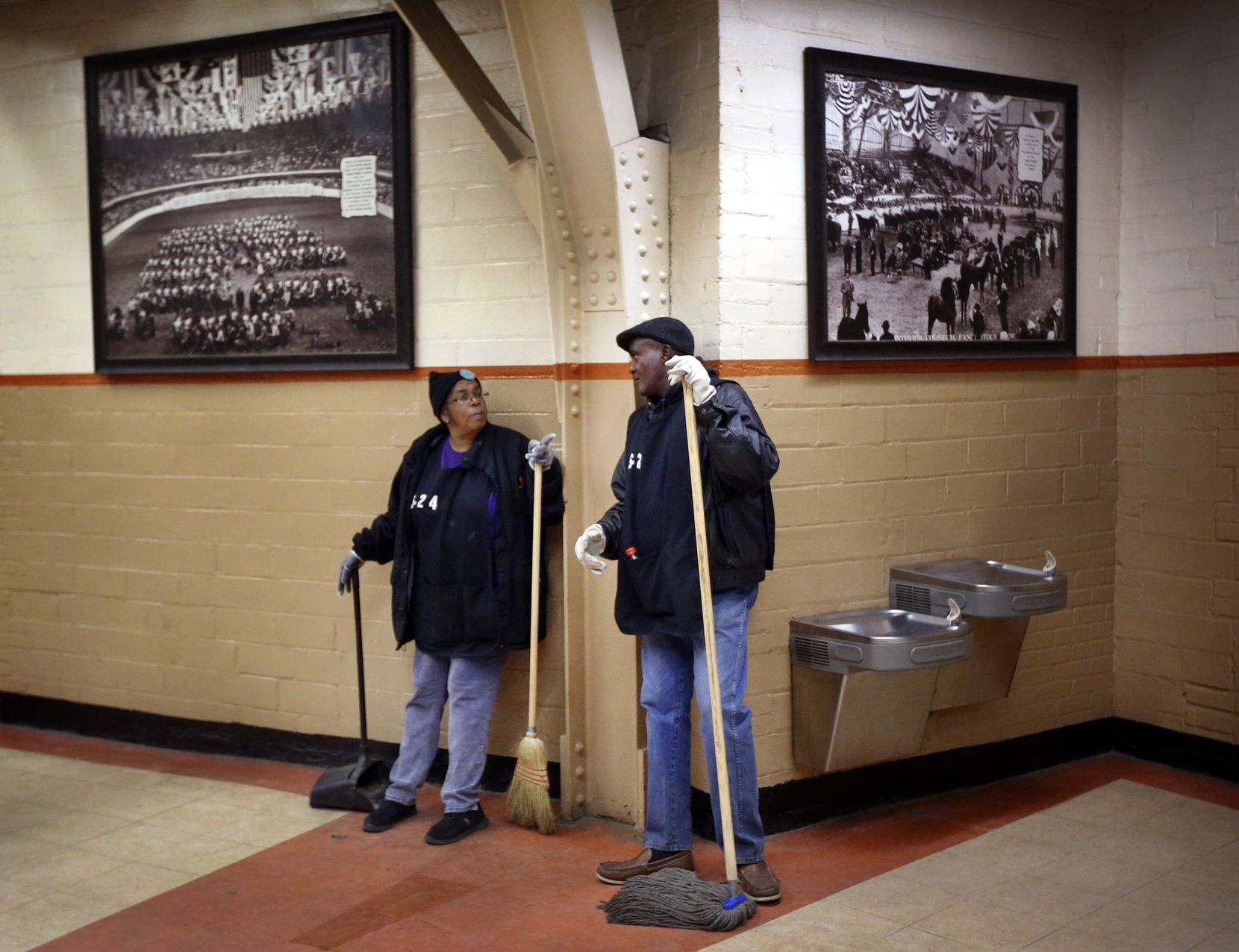 A pair of custodians visit along the historic, photo-lined walls of Will Rogers Memorial Coliseum, Thursday, January 31, 2019.