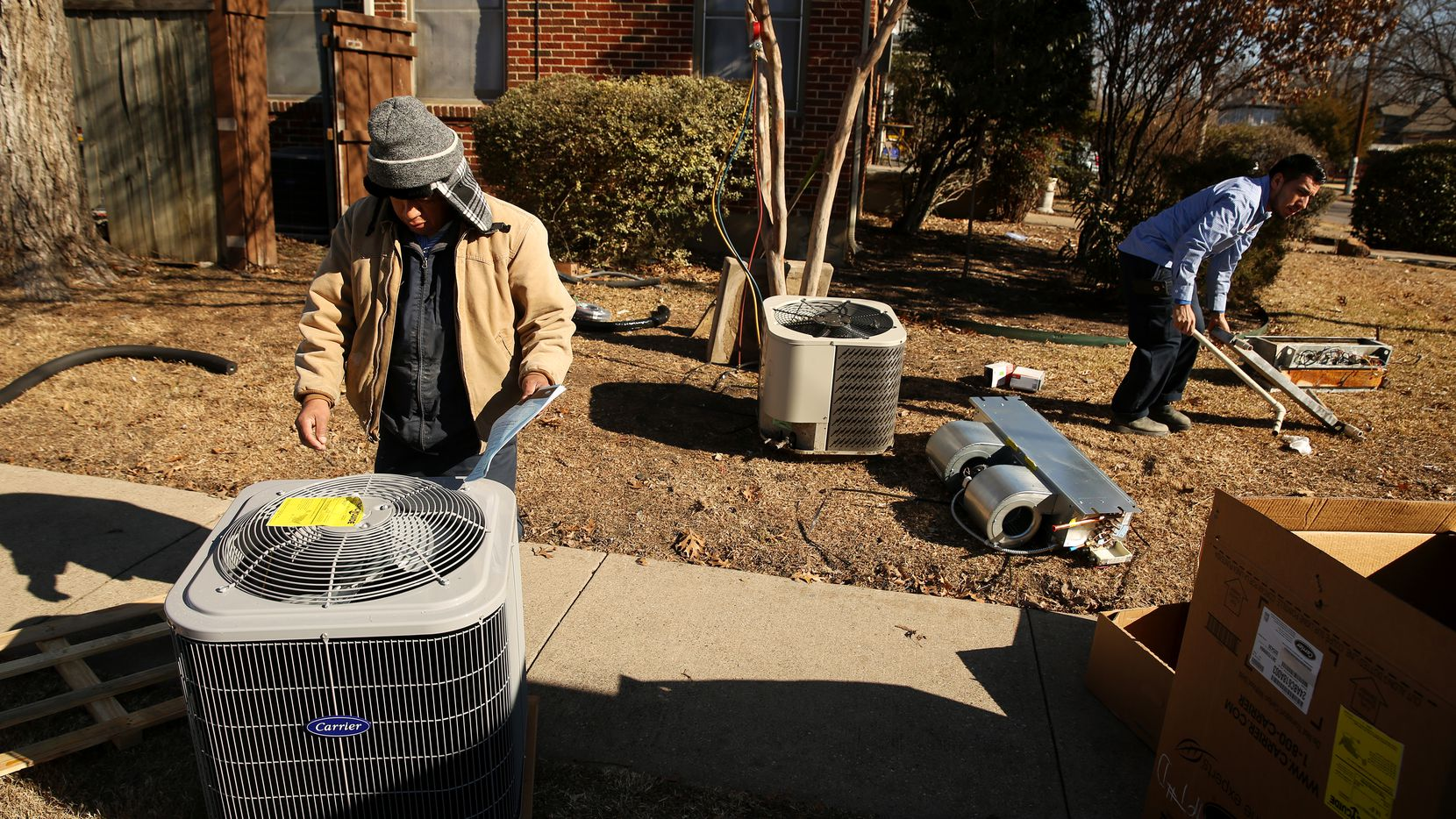 Lorenzo Rios (left) and Gabriel Garcia of Reliant Air Conditioning install a new air conditioning unit at a residence on the corner of East Side Avenue and Henderson Avenue.