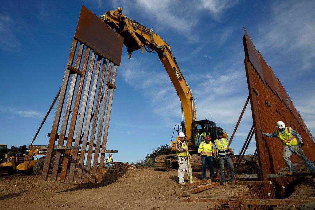 "FILE - In this Jan. 9, 2019 file photo, construction crews install new border wall sections seen from Tijuana, Mexico. Sen. Dick Durbin, D-Ill., says the Pentagon is planning to tap $1 billion in leftover funds from military pay and pensions accounts to help President Donald Trump pay for his long-sought border wall. Durbin told The Associated Press, ""it's coming out of military pay and pensions, $1 billion, that's the plan.""(AP Photo/Gregory Bull, File)"