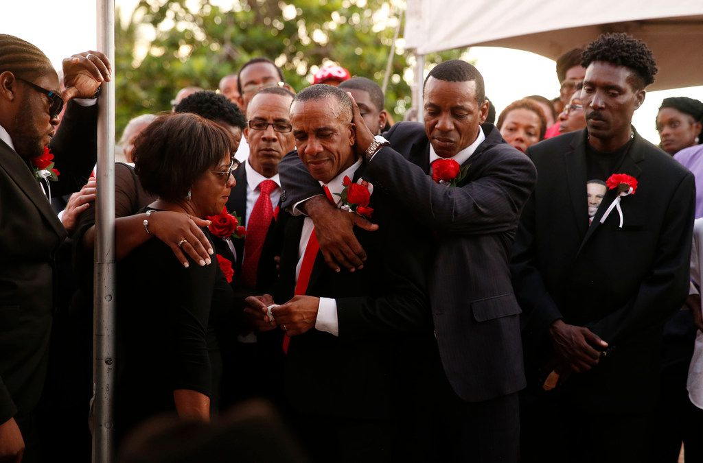 Allison (hidden) and Bertrum Jean hug as they surrounded by family and friends as their son Botham Shem Jean is buried at Choc Cemetery in Castries, St. Lucia Sept. 24, 2018. Jean was shot and killed in his apartment by off duty Dallas police officer Amber Guyger. Guyger was fired the same day Jean was buried in the cemetery overlooking the Caribbean Sea.