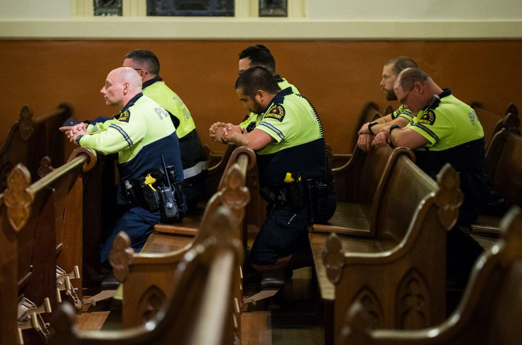 Dallas police officers kneel during a mass in which Father Angel Torres offered a special prayer for Dallas Police Officer Rogelio Santander and other shooting victims on April 25, 2018 in Dallas. Santander was shot and killed outside of a Home Depot in Lake Highlands on Tuesday. Officer Crystal Almeida and Home Depot employee Scott Painter were also shot and they remain in critical condition. (Ashley Landis/The Dallas Morning News)