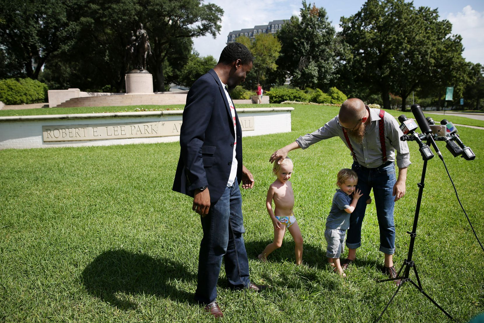 The Rev. Dr. Jeff Hood greets his children, Jeff Hood Jr. and Quinley Mandela Hood, as their father and minister Dominique Alexander speak to reporters about the Confederate statue removal efforts Aug. 18, 2017. Hood and Alexander were calling into question Dallas Mayor Mike Rawlings calling for a task force to look into the issue of removing public Confederate monuments.