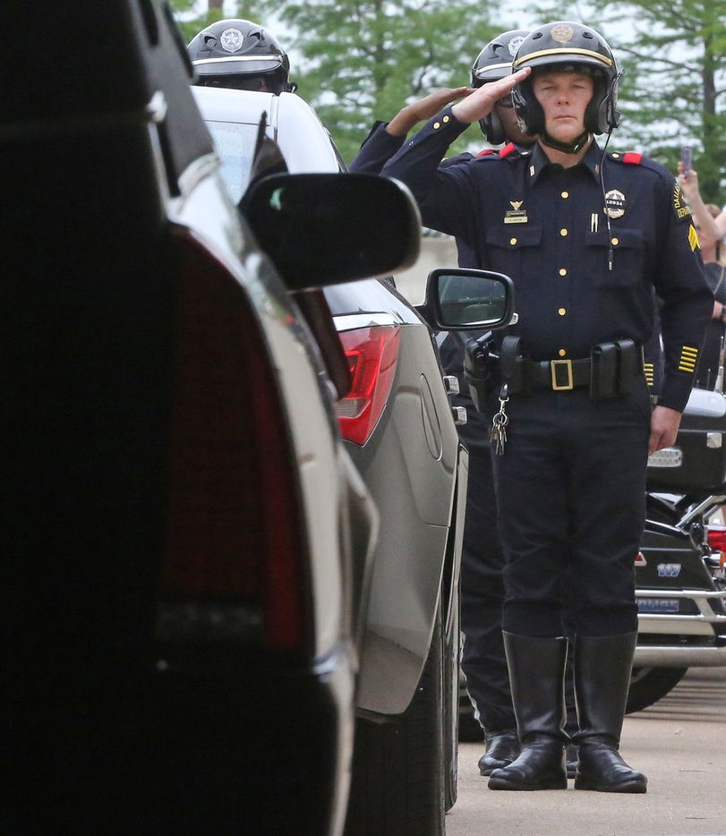 Law enforcement officers salute as the body of Dallas Officer Rogelio Santander is loaded into the hearse at Lake Pointe Church in Rockwall.