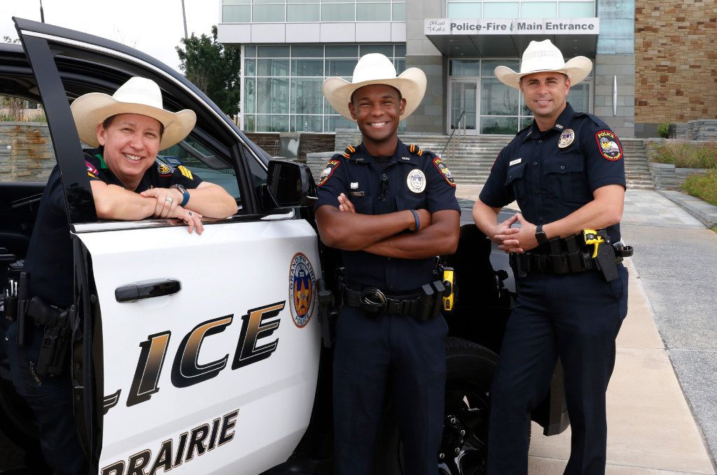 Grand Prairie police officers Sgt. Brandy Elliott (from left), Louis Johnson and Mark Beseda sport their new cowboy hatsat the Grand Prairie police headquarters.