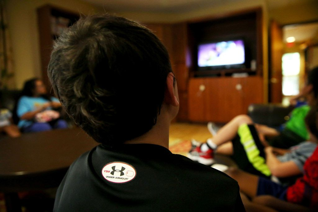 A boy watches TV at Jonathan's Place, which serves abused and neglected children, in Garland on June 30, 2017. (Rose Baca/The Dallas Morning News)