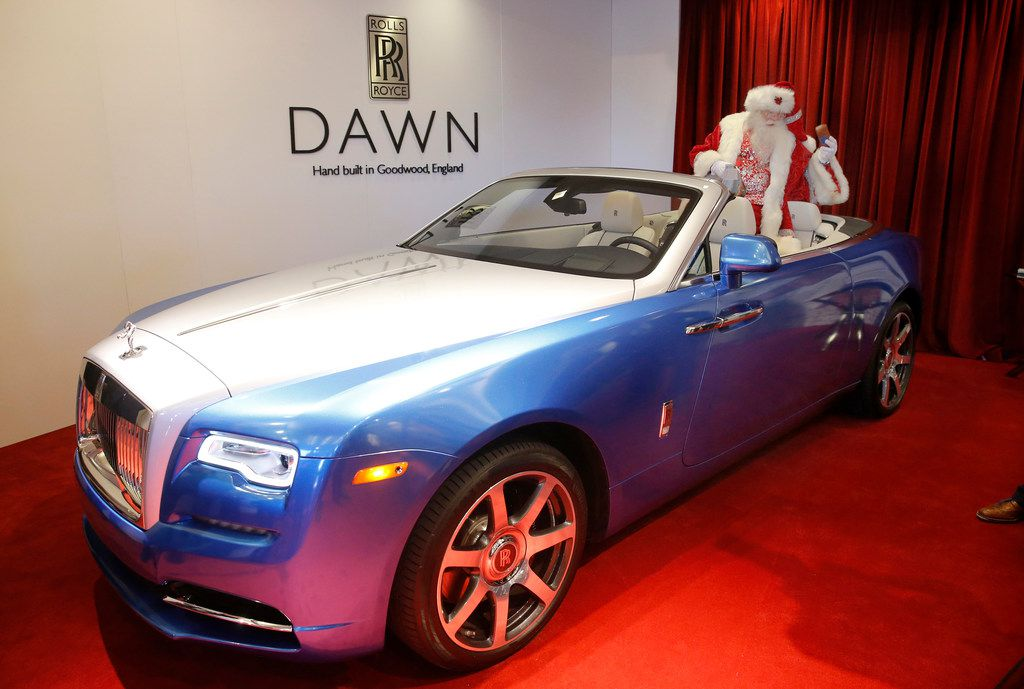 Santa Claus sits in one of the Yours & Mine Exclusive Rolls-Royce Dawn Drophead Coupes that was featured at the Neiman Marcus' Christmas Book Fantasy Gift Reveal at the Park Place Premier Collection in Dallas in October. His version here in Coniston Blue sells for $439,625, hers in a Saint-Tropez Orange sells for $445,750.