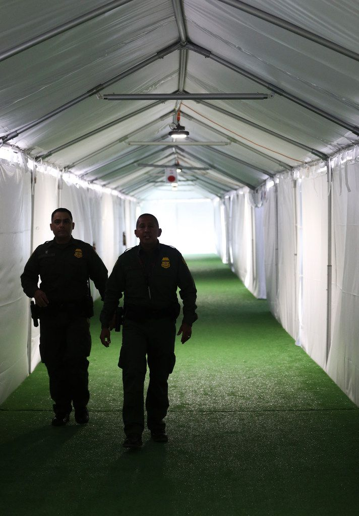 U.S. Border Patrol agents walk the hallway of a temporary holding facility near the Donna-Rio Bravo International Bridge on Thursday, May 2, 2019 in Donna, Texas. Officials say the soft-sided tent facility will primarily be used as a temporary site for processing and care of asylum seekers crossing the border and will increase the Border Patrol's capacity to process migrant families while they await transfer to U.S. Immigration and Customs Enforcement or to the Department of Health and Human Services. (Ryan Michalesko/The Dallas Morning News)