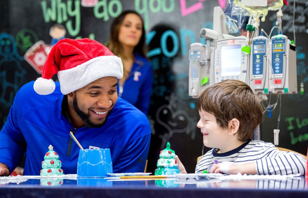 Texas Rangers shortstop Elvis Andrus laughs with Sebastian Gardner, 5, while they paint ceramic Christmas trees during a visit to Children's Medical Center of Dallas on Dec. 19, 2017.