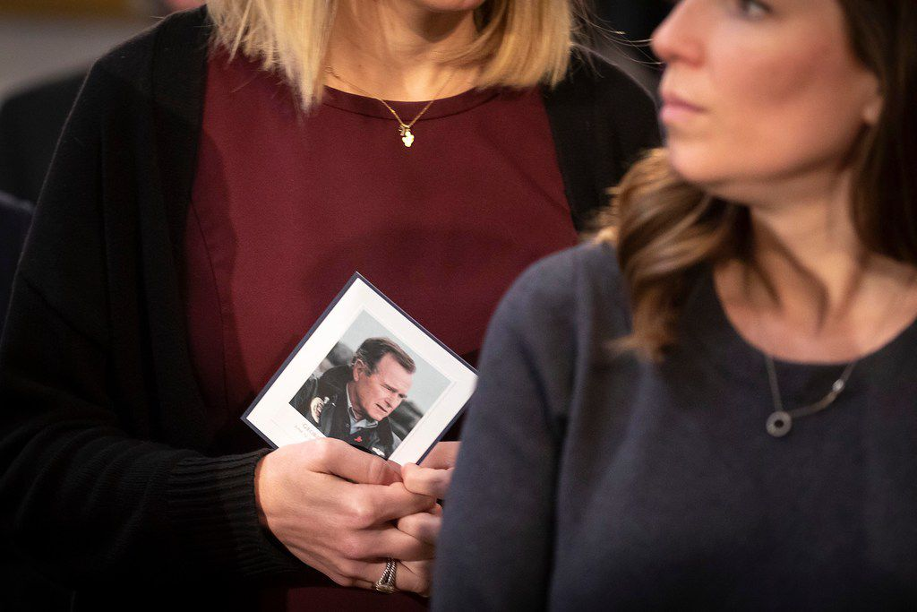 Mourners clutch cards in memory of President George H.W. Bush as he lies in the Rotunda of the U.S. Capitol on Tuesday, Dec. 4, 2018, in Washington.