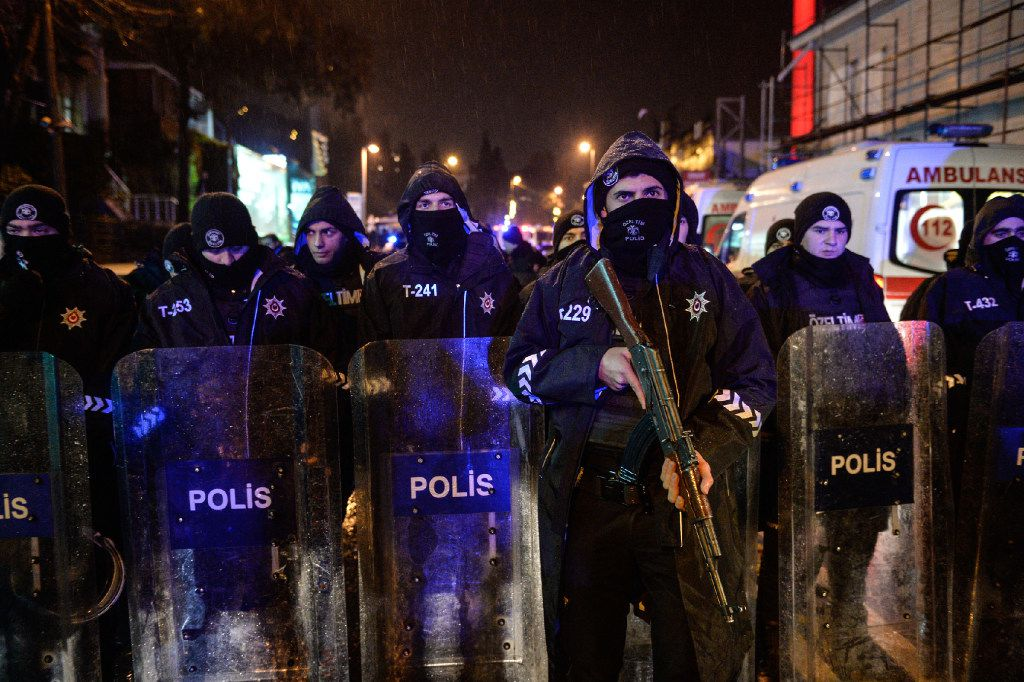 Turkish police officers block the road leading to the scene of an attack in Istanbul, early Sunday, Jan. 1, 2017. An assailant believed to have been dressed in a Santa Claus costume and armed with a long-barrelled weapon, opened fire at a nightclub in Istanbul's Ortakoy district during New Year's celebrations, killing dozens of people and wounding dozens of others in what the province's governor described as a terror attack. (Depo Photos via AP)