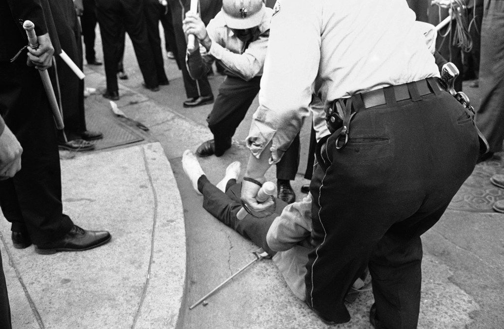 "From the Associated Press caption that accompanies this archival photo: ""Police in Jackson, Miss., club Willie Ludden Jr. of Atlanta after he resisted arrest during massive demonstration, May 31, 1963.  Ludden carried a sign and American flag in the march."""