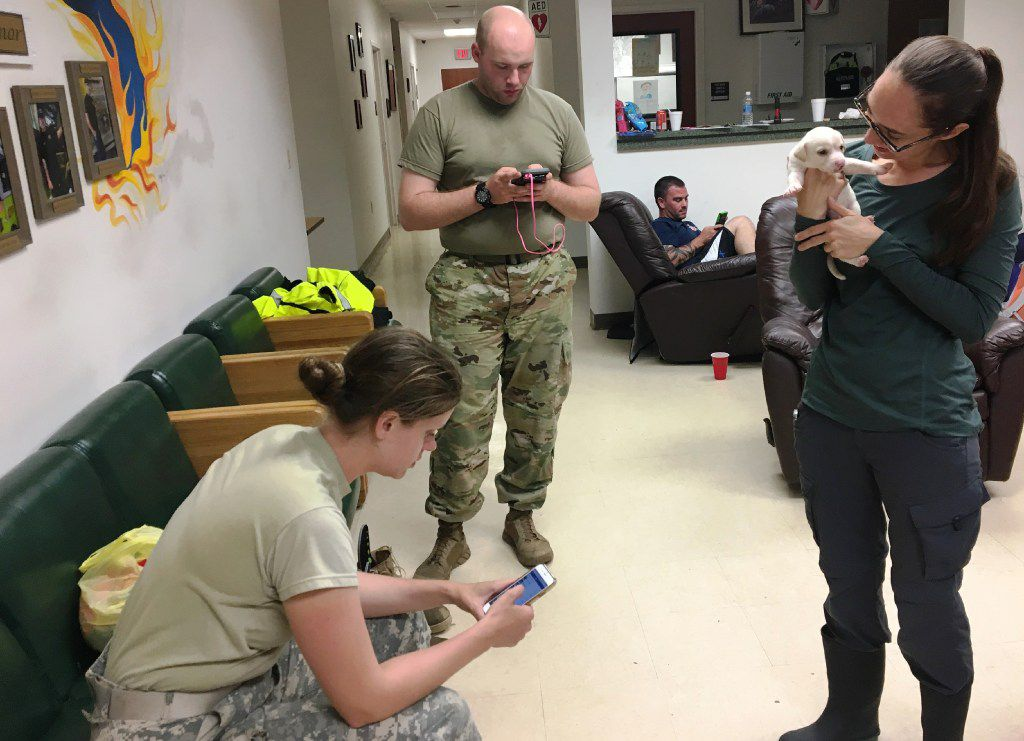 Dallas Morning News photographer Ashley Landis holds a puppy at the Lumberton fire station as National Guard Specialist Kyleigh Neese, left, and Private First Class Luke Lee, center, hang out on Wednesday, August 30, 2017. (Naomi Martin/ Staff)
