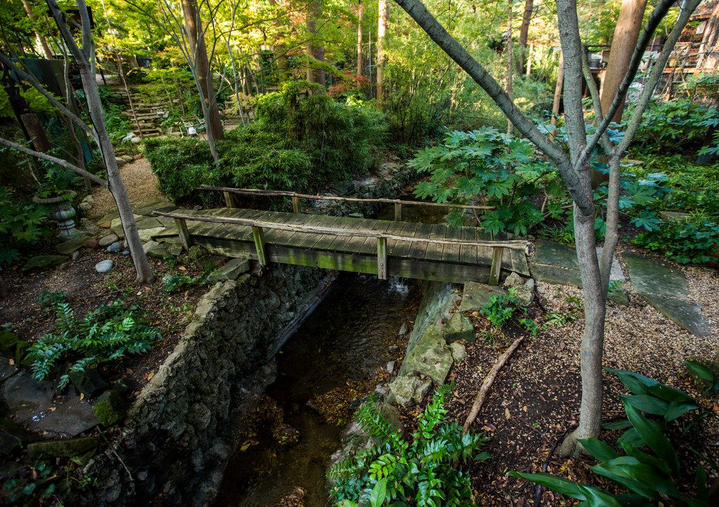 """A wooden bridge that leads over a creek and to the front door of an Airbnb house affectionately known as the """"tree house"""" and named the most wish-listed Airbnb in Dallas."""