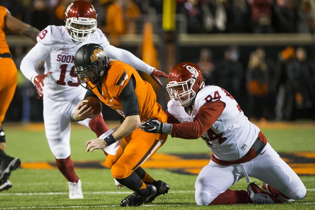 Oklahoma State quarterback J.W. Walsh (4) is sacked by Oklahoma defensive end Matt Dimon (94) during the first quarter of an NCAA football game at Boone Pickens Stadium on Saturday, Nov. 28, 2015, in Stillwater, Okla. (Smiley N. Pool/The Dallas Morning News)
