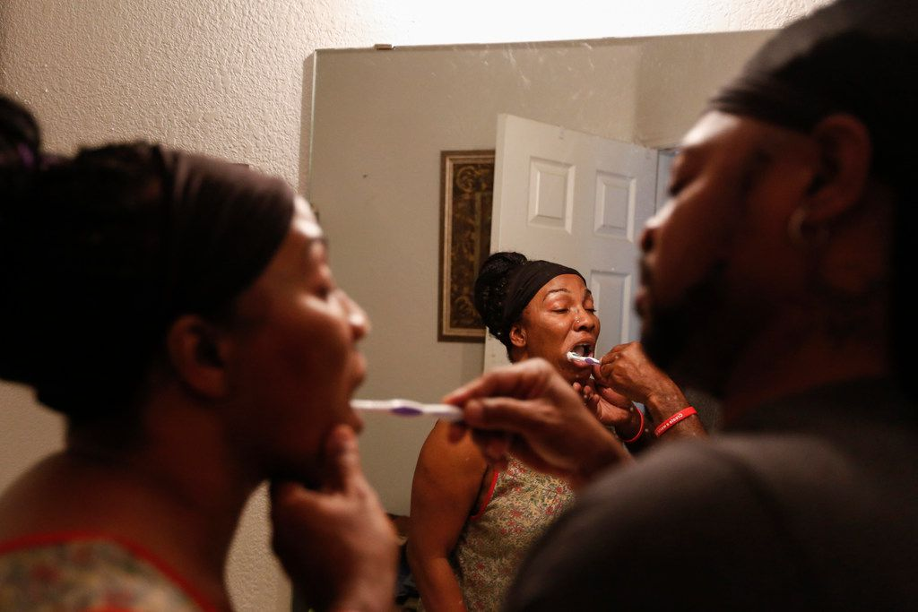 Samantha Barber opens her mouth so her husband Terrence can brush her teeth.