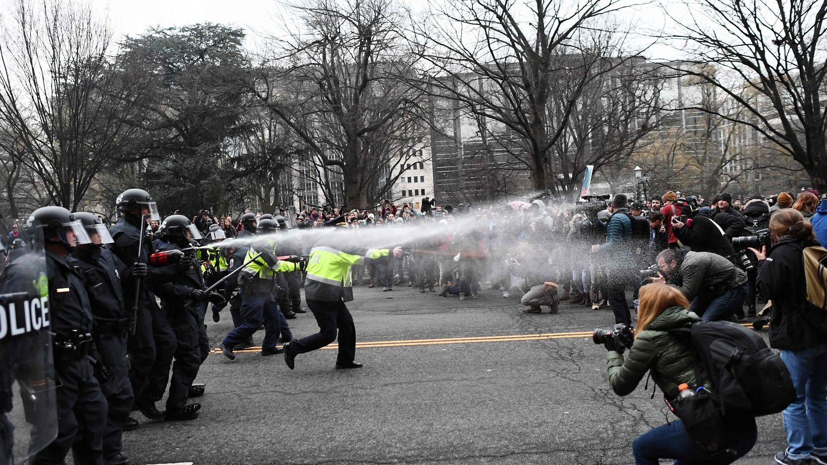 TOPSHOT - Police pepper spray at anti-Trump protesters during clashes in Washington, DC, on January 20, 2107.   Masked, black-clad protesters carrying anarchist flags smashed windows and scuffled with riot police Friday in downtown Washington, blocks away from the route of the parade in honor of newly sworn-in President Donald Trump. Washington police arrested more than 90 people over acts of vandalism committed on the fringe of peaceful citywide demonstrations being held against Trump's inauguration. / AFP PHOTO / Jewel SAMADJEWEL SAMAD/AFP/Getty Images