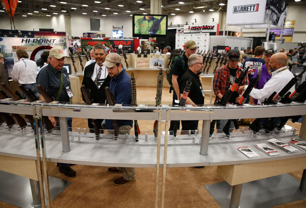 Men look at scopes at the NRA Annual Meeting & Exhibits at Kay Bailey Hutchison Convention Center in Dallas on Friday.