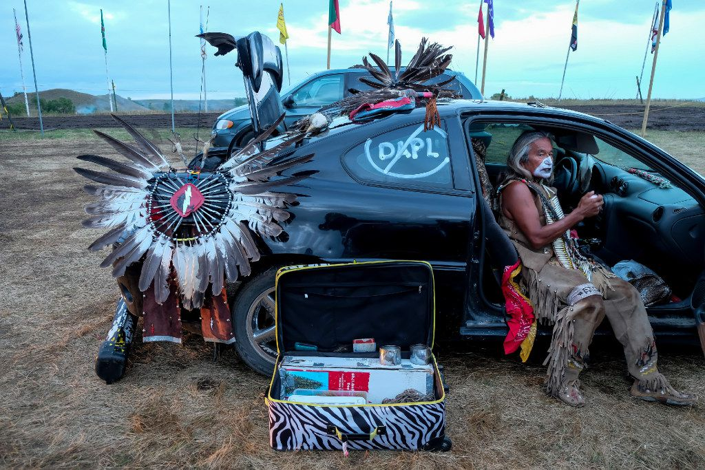 Little Thunder, a traditional performer, is doing makeup before started dance inside of his car at Oceti Sakowin Camp in Cannonball, North Dakota on Thursday, Sep15th, 2016.  Standing Rock has seen hundreds of whole families and activists visit, eager to take part in the historic gathering.  Construction has been halted after the Obama administration decision to suspend construction on a controversial oil pipeline in North Dakota.  (Jeenah Moon/Special Contributor)