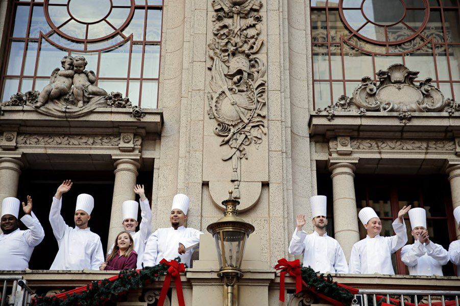 Cooks from The Adolphus hotel wave during the Dallas Children's Health Holiday Parade in December 2014.