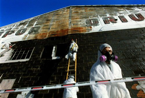 Pedro Enriquez (right) and other workers from L.A. Environmental Inc. stripped asbestos-laden shingles from the exterior of the Sportatorium to prepare it for demolition in 2003.
