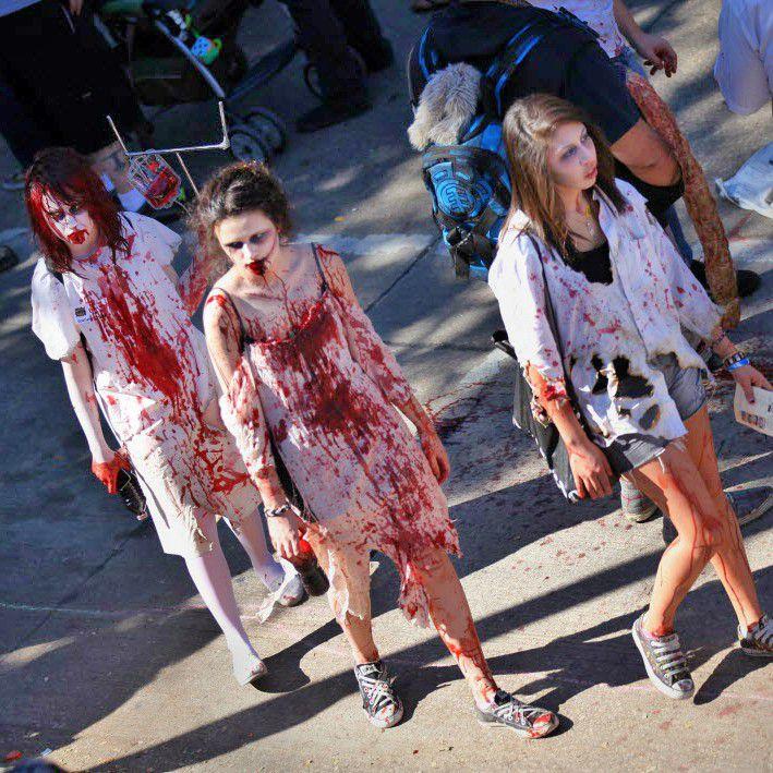 Three women dressed as zombies walk through Deep Ellum during Zombie Walk.
