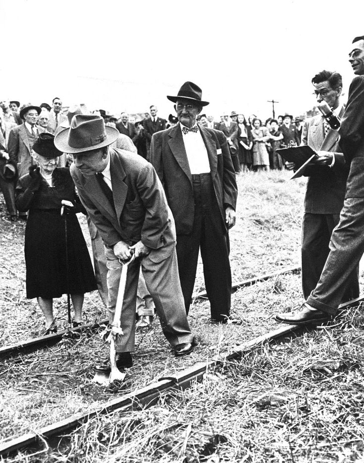 Groundbreaking for The News' new Young Street building. Mrs. G. B. [Olivia] Dealey (left) watches Senior Vice President Joe Lubben break ground Oct. 17, 1946. Columnist Paul Crume is holding a clipboard.