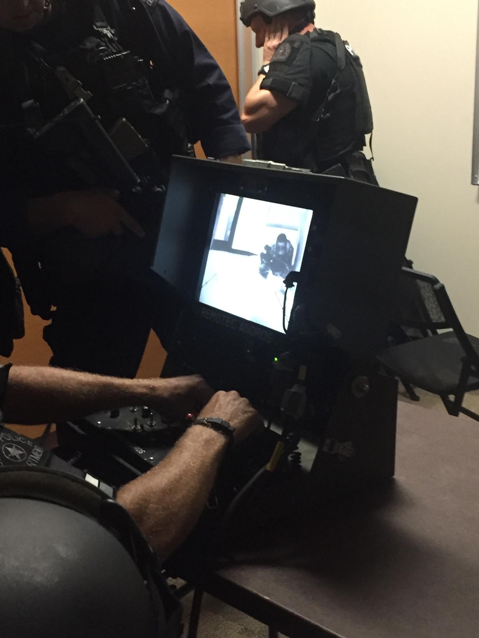 Jeremy Borchardt manejó el robot-bomba a control remoto. En esta foto de SWAT se observa a Matt Renfro (quien armó 90% de la bomba) tapándose los oídos. En el video se ve a Micah Johnson mirando por encima del robot.